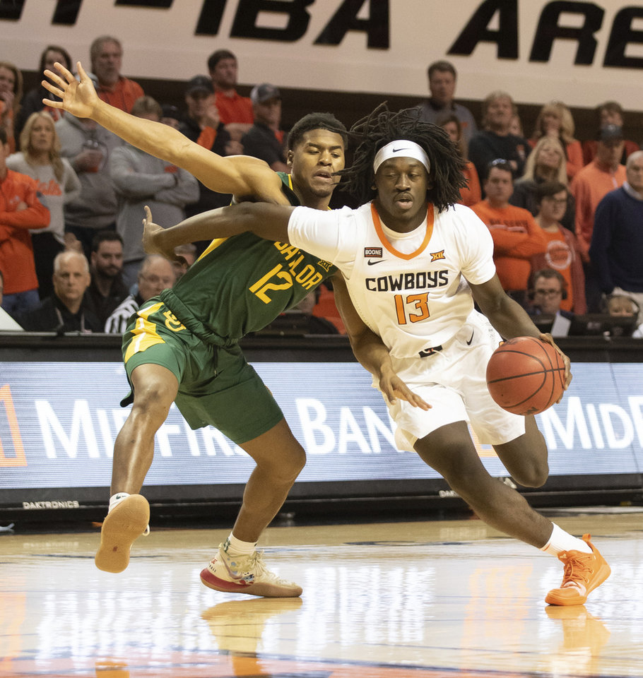 Photo - Oklahoma State guard Isaac Likekele (13) drives past Baylor guard Jared Butler (12) during an NCAA college basketball game in Stillwater, Okla., Saturday, Jan. 18, 2020. (AP Photo/Brody Schmidt)