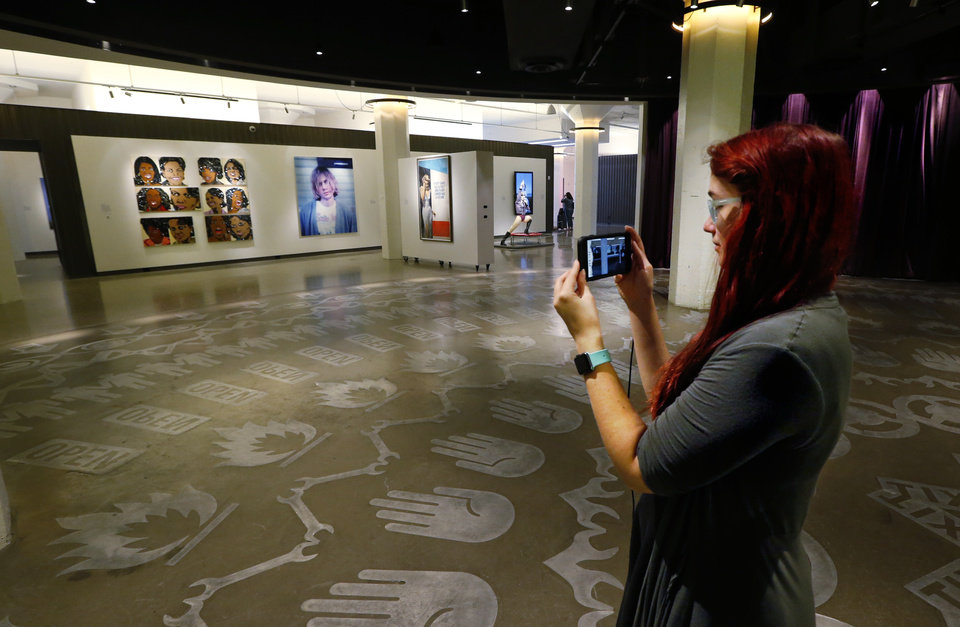Photo -  Kenna Jackson, with Trifecta Communications, observes the 21c Museum Hotel building as it would have appeared in 1916 through an app on her phone. [Photo by Steve Sisney]