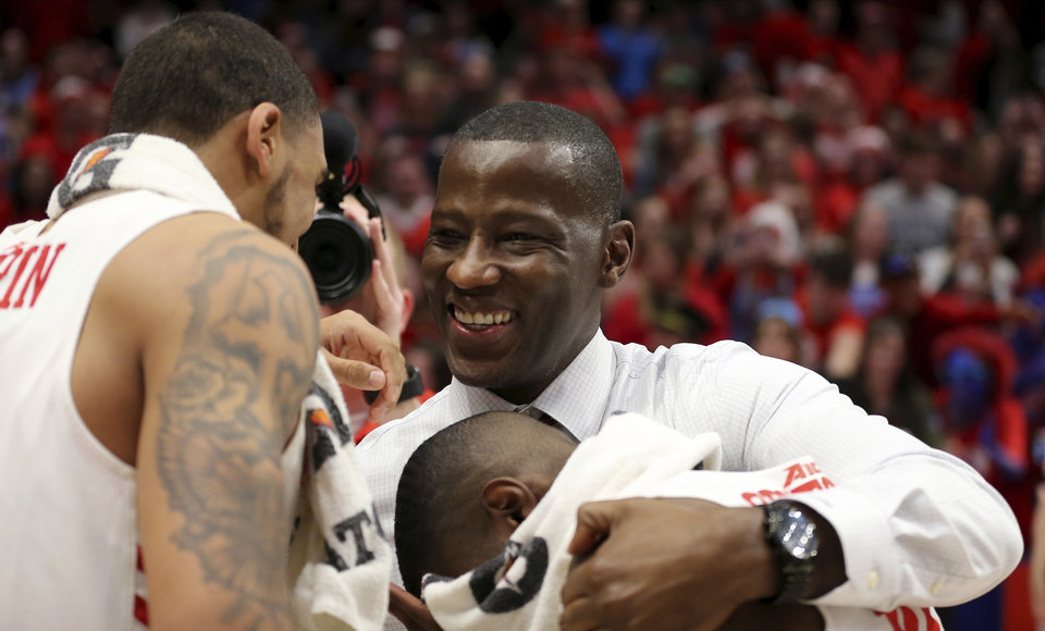Photo - FILE - In this March 7, 2020, file photo, Dayton head coach Anthony Grant celebrates with Obi Toppin, left, and Jalen Crutcher, bottom right, after their win in an NCAA college basketball game against George Washington, in Dayton, Ohio. Toppin and Grant have claimed top honors from The Associated Press after leading the Flyers to a No. 3 final ranking. Toppin was voted the AP men's college basketball player of the year, Tuesday, March 24, 2020. Grant is the AP coach of the year. (AP Photo/Tony Tribble, File)