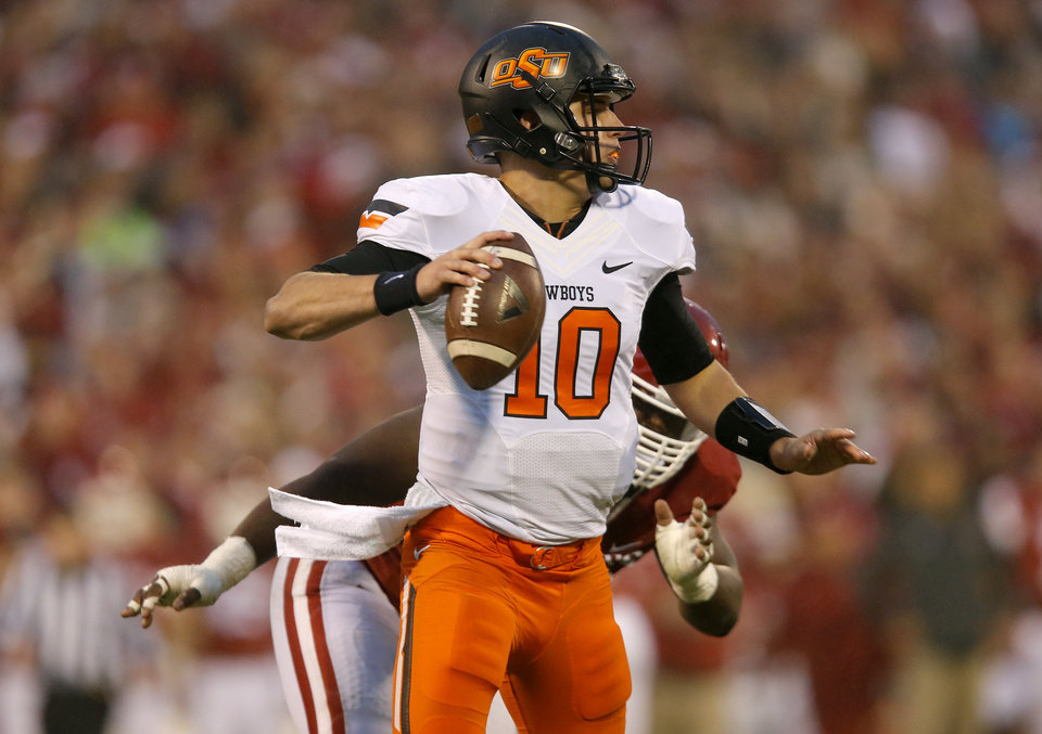 Photo - Oklahoma State's Mason Rudolph (10) looks to pass as he is pressured during the Bedlam college football game between the University of Oklahoma Sooners (OU) and the Oklahoma State Cowboys (OSU) at Gaylord Family-Oklahoma Memorial Stadium in Norman, Okla., Saturday, Dec. 6, 2014. Photo by Sarah Phipps, The Oklahoman