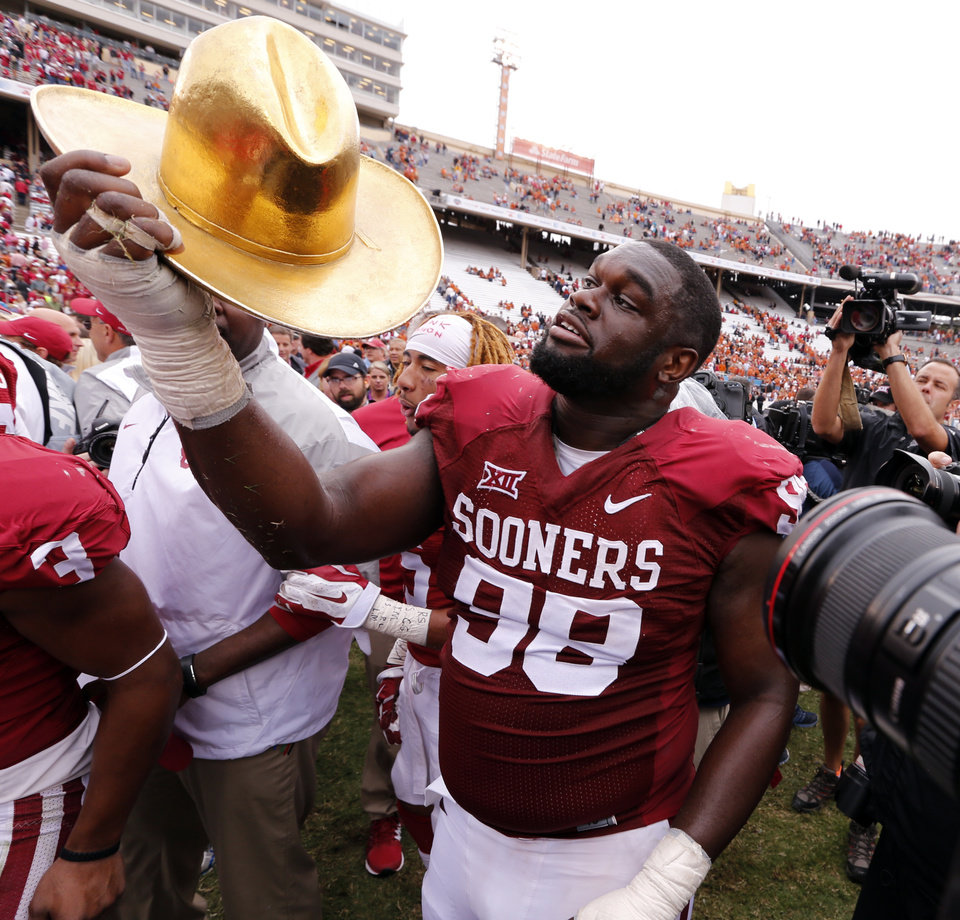 Photo - Oklahoma's Chuka Ndulue dons the Golden Hat trophy after the Red River Showdown college football game where the University of Oklahoma Sooners (OU) defeated the University of Texas Longhorns (UT)  31-26 at the Cotton Bowl in Dallas, Texas on Saturday, Oct. 11, 2014. 