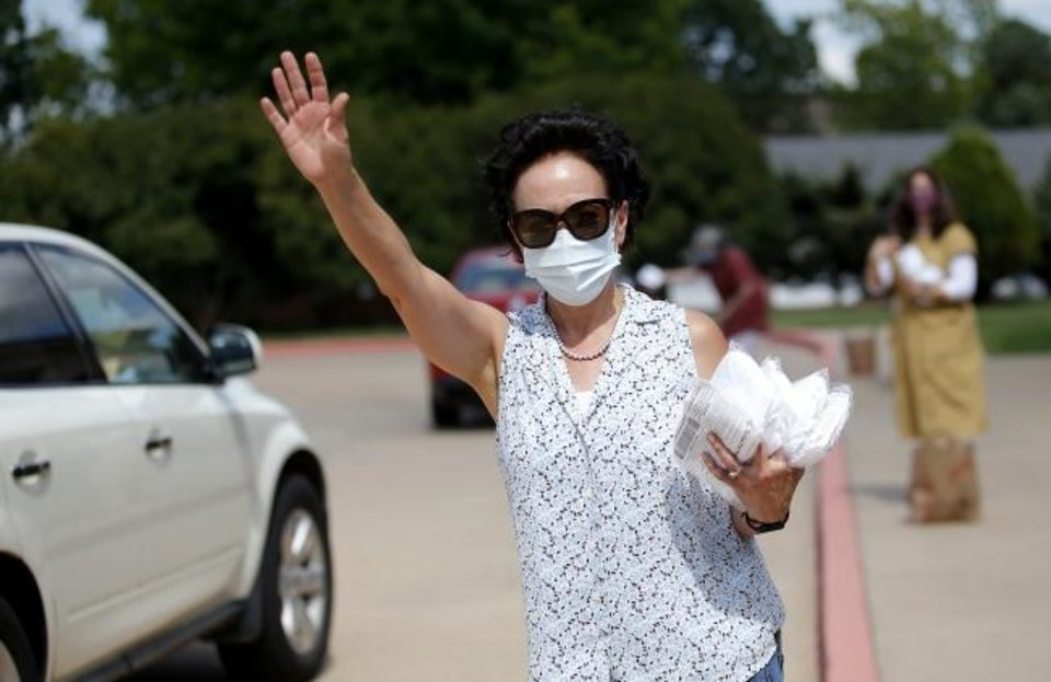 Photo -  Village City Councilwoman Cathy Cummings waves to motorists  during a drive-thru mask distribution at Chabad Community Center for Jewish Life and Learning, 3000 W Hefner Road. [Sarah Phipps/The Oklahoman]