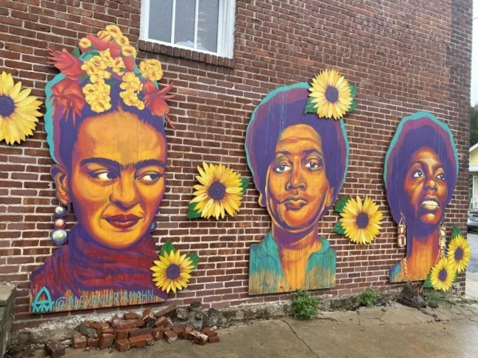Photo -  An exterior wall of Fulton Street Books & Coffee features colorful images of well known women of color, including Mexican artist Frida Kahlo, writer Audre Lorde and singer-songwriter Nina Simone.[Carla Hinton/The Oklahoman]