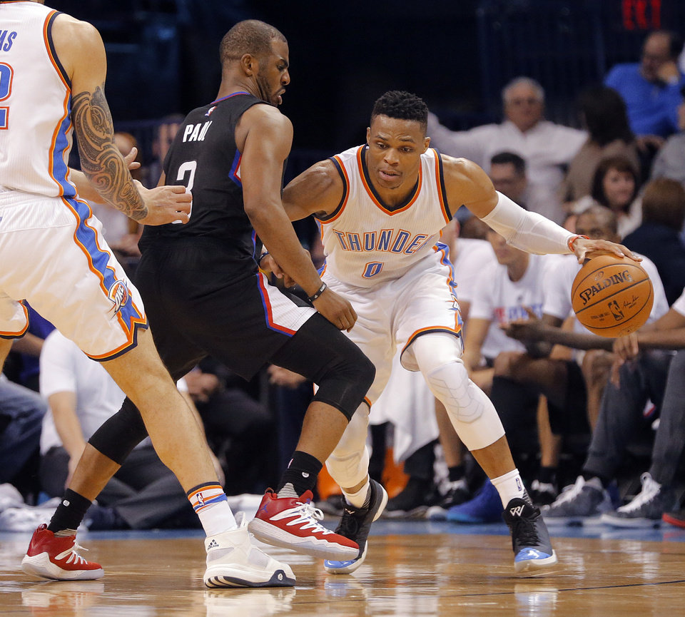 Photo - Oklahoma City's Russell Westbrook (0) drives past Los Angeles Clippers' Chris Paul (3) during the NBA basketball game between the Oklahoma City Thunder and the Los Angeles Clippers at Chesapeake Energy Arena on Wednesday, March 9, 2016, in Oklahoma City, Okla. Photo by Chris Landsberger, The Oklahoman