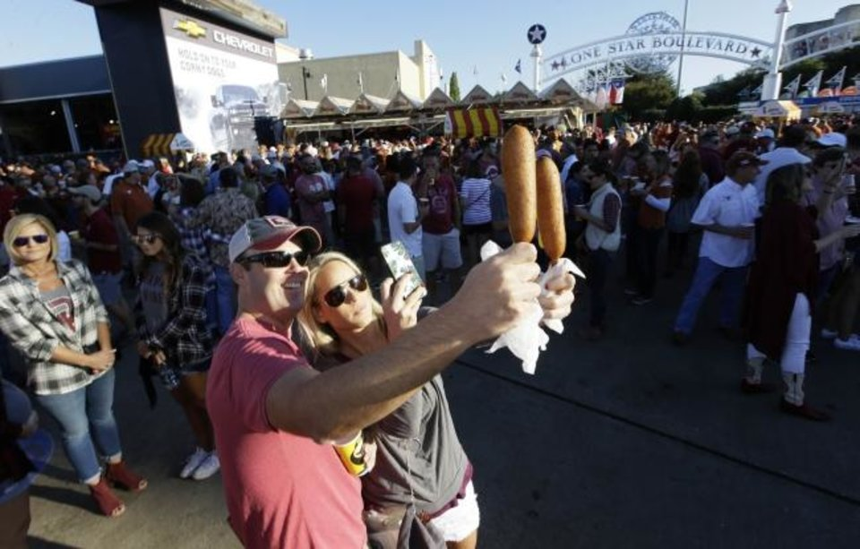 Photo -  Fletcher's corny dogs are photogenic and a rite of passage for OU and Texas fans every October at the State Fair of Texas outside Cotton Bowl Stadium in Dallas with nearly half a million sold each fall. [AP Photo/LM Otero]