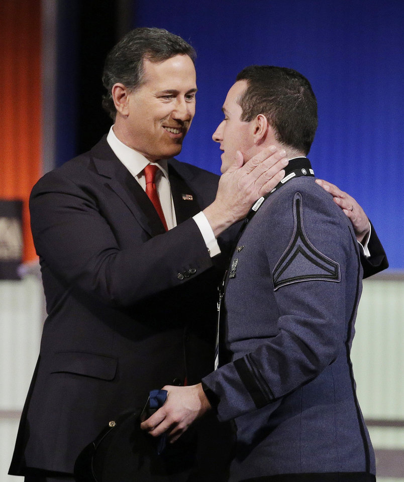 Photo - Republican presidential candidate, former Pennsylvania Sen. Rick Santorum embraces his son Daniel Santorum, a cadet at the Citadel after the Fox Business Network Republican presidential debate at the North Charleston Coliseum, Thursday, Jan. 14, 2016, in North Charleston, S.C. (AP Photo/Chuck Burton)