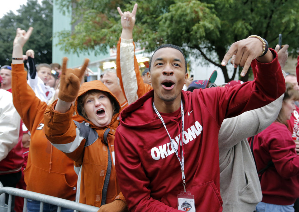 Photo - Texas fan Linda Culpepper and Oklahoma fan Wynton Carter show their opposing views as the Texas team bus arrives for the college football game between the University of Oklahoma Sooners (OU) and the University of Texas Longhorns (UT) during the Red River Showdown at the Cotton bowl in Dallas, Texas on Saturday, Oct. 11, 2014. Photo by Chris Landsberger, The Oklahoman