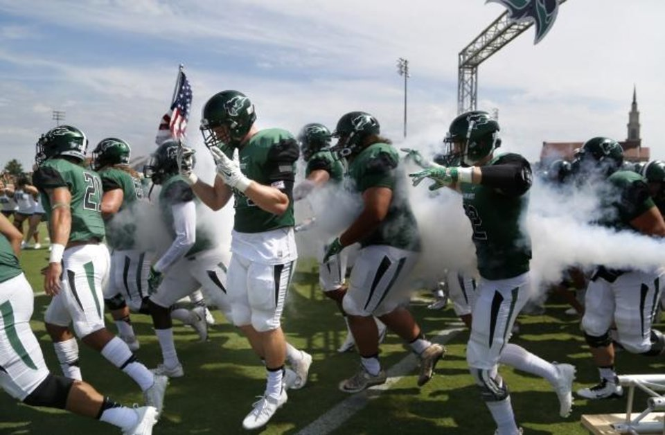 "Photo -  Pictured: The Oklahoma Baptist football team runs out on to the field before a 2017 game. OBU athletic director Robert Davenport says of fall sports, ""right now it's 50-50 we push it to spring,"" but that is fraught with problems, too. [Sarah Phipps/The Oklahoman]"