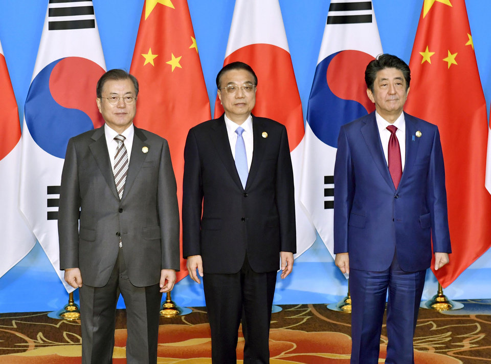 Photo -  CORRECTS POSITIONS - Chinese Premier Li Keqiang, center, Japan's Prime Minister Shinzo Abe, right, and South Korean President Moon Jae-in, left, pose for a group photo before the trilateral meeting between China, South Korea and Japan in Chengdu, southwest China's Sichuan province Tuesday, Dec. 24, 2019. (Yoshitaka Sugawara/Kyodo News via AP)