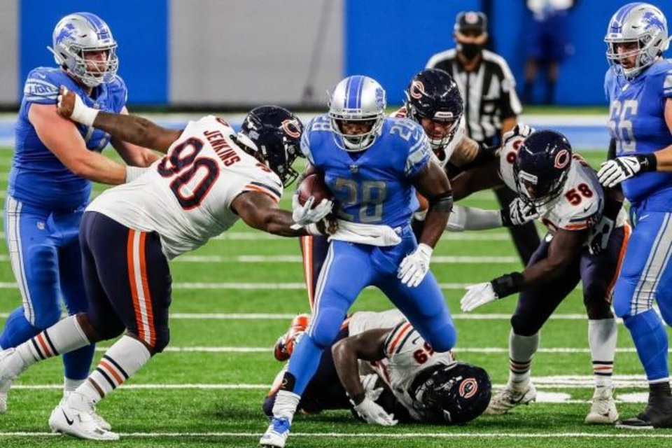 Photo -  Lions running back Adrian Peterson breaks through the Bears' defense Sunday in a 27-23 loss at Ford Field in Detroit. [Junfu Han/Detroit Free Press]