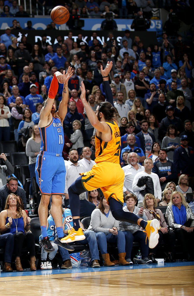 Photo - Oklahoma City's Abdel Nader (11) shoots a 3-point basket over Utah's Ricky Rubio (3) during the NBA game between the Oklahoma City Thunder and the Utah Jazz at the Chesapeake Energy Arena, Friday, Feb. 22, 2019. Photo by Sarah Phipps, The Oklahoman