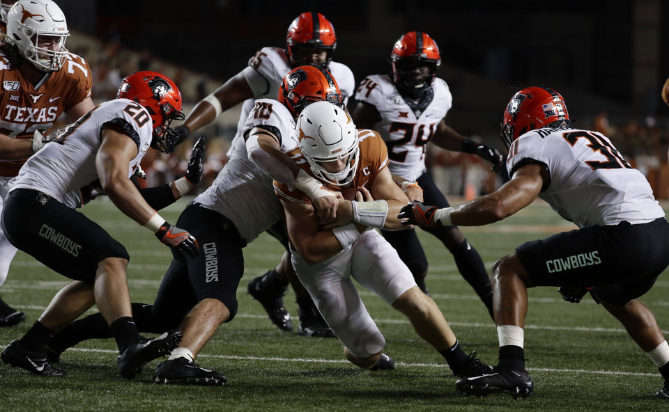 Photo - Texas quarterback Sam Ehlinger (11) is stopped by Oklahoma State defensive end Brock Martin (40) on a run during the second half of an NCAA college football game Saturday, Sept. 21, 2019, in Austin, Texas. (AP Photo/Eric Gay)