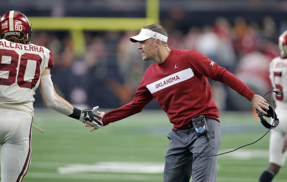 Photo - Oklahoma coach Lincoln Riley celebrates with Oklahoma's Grant Calcaterra (80) after a touchdown during the Big 12 Championship football game between the Oklahoma Sooners (OU) and the Texas Longhorns (UT) at AT&T Stadium in Arlington, Texas, Saturday, Dec. 1, 2018.  Oklahoma won 39-27. Photo by Bryan Terry, The Oklahoman