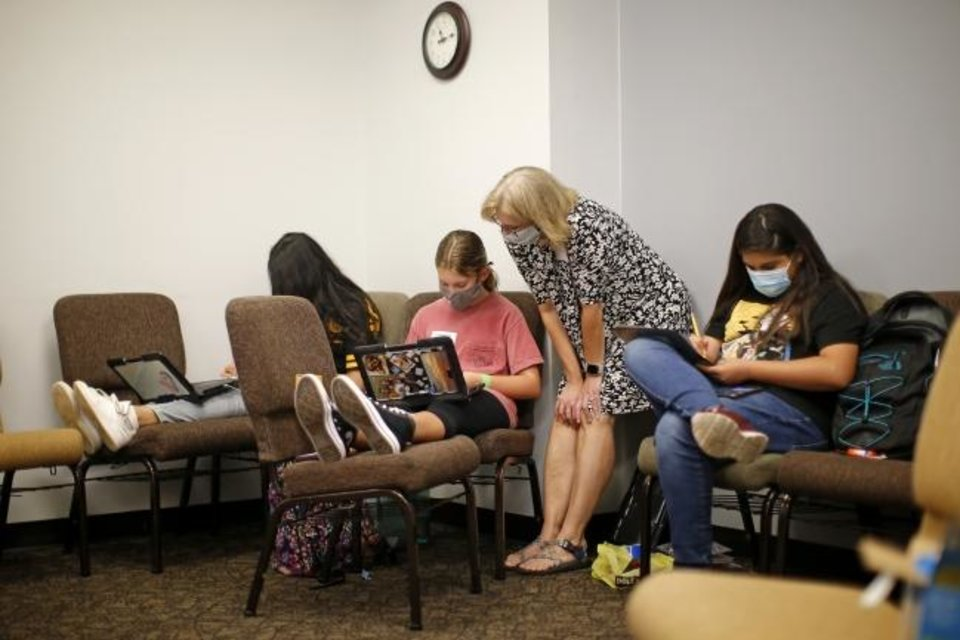 Photo -  A volunteer helps students study on Wednesday at Henderson Hills Baptist Church in Edmond. [Bryan Terry/The Oklahoman]