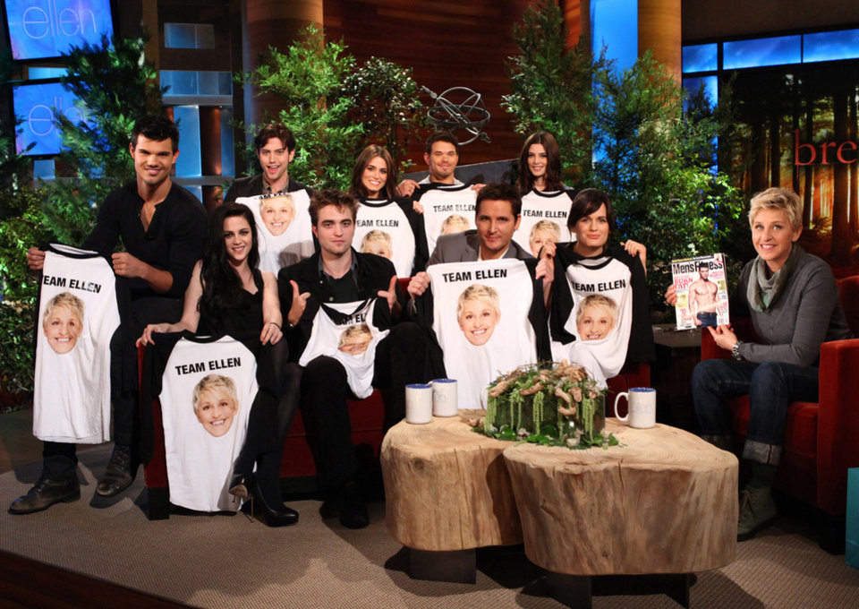 Photo - In this Nov. 14, 2011 photo released by Warner Bros., talk show host Ellen DeGeneres, right, holds up an issue of Men's Fitness as she welcomes the cast of
