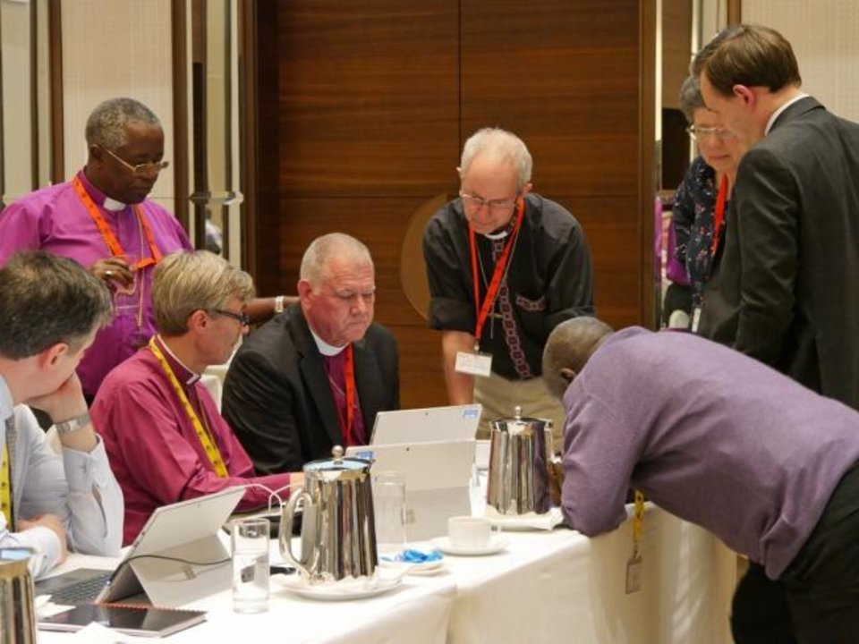 Photo -  Diocese of Nairobi Bishop Joel Waweru looks over the shoulder of the Rt. Rev. Ed Konieczny as the Archbishop of Canterbury Justin Welby looks on at an Anglican Communion gathering in Hong Kong. [Mary Frances Schjonberg/Episcopal News Service]