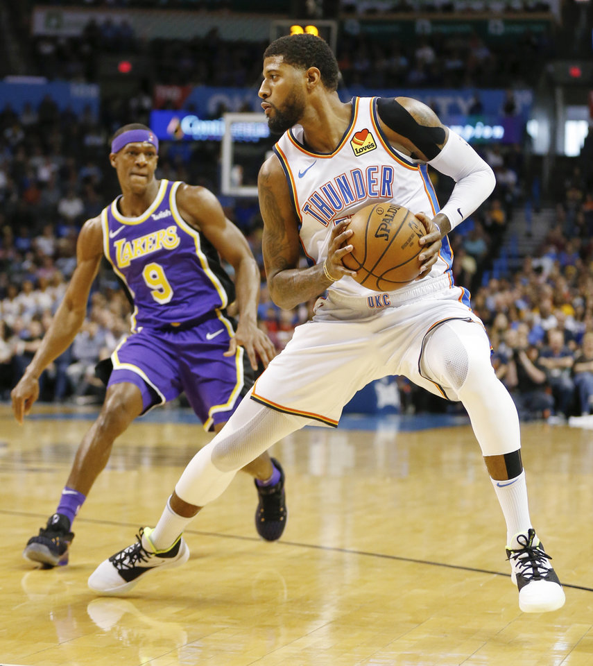 Photo - Oklahoma City's Paul George (13) steps back for a shot in the first quarter near Los Angeles' Rajon Rondo (9) during an NBA basketball game between the Los Angeles Lakers and the Oklahoma City Thunder at Chesapeake Energy Arena in Oklahoma City, Tuesday, April 2, 2019. Photo by Nate Billings, The Oklahoman