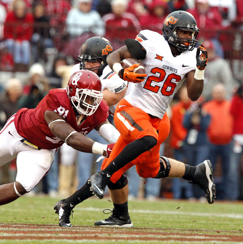 Photo - Cowboy's Desmond Roland (26) carries during a Bedlam college football game between the University of Oklahoma Sooners (OU) and the Oklahoma State Cowboys (OSU) at Gaylord Family-Oklahoma Memorial Stadium in Norman, Okla., on Saturday, Dec. 6, 2014. Photo by Steve Sisney, The Oklahoman