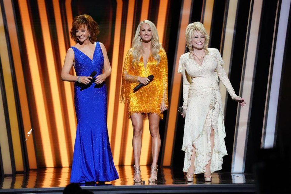 Photo - Carrie Underwood, center, with special guest hosts Dolly Parton, right, and Reba McEntire, host the 53rd Annual CMA Awards live from Bridgestone Arena in Nashville Wednesday, November 13 on ABC. [John Russell/CMA]