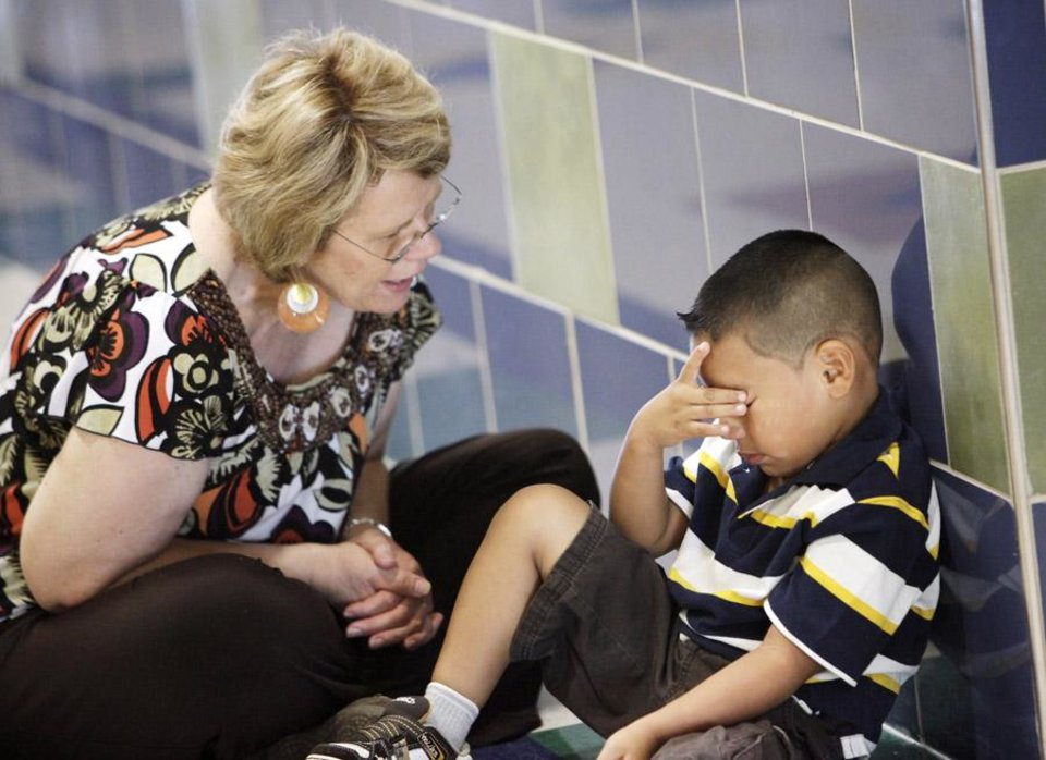 Photo -  School principal JoAnn Simpson-Miller talks with a distraught Jorge Gonzales, 5, as he sits on the floor outside his kindergarten classroom at Sunset Elementary School on the first day of classes in Edmond Thursday, August 19, 2010. Photo by Paul B. Southerland, The Oklahoman
