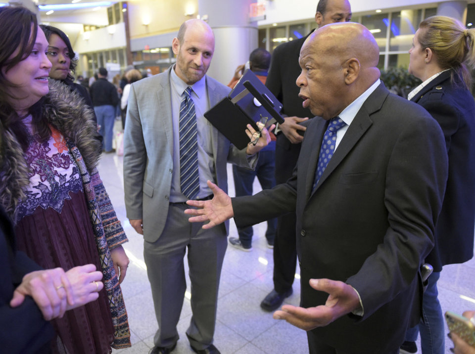 Photo - U.S. Congressman John Lewis, right, (D-Ga.) speaks with attorneys Sarah Owings and Daniel Werner outside the  U.S. Customs and Border Protection office at Hartsfield-Jackson Atlanta International Airport, Saturday, Jan. 25, 2017.  Several people were detained earlier today after an executive order from President Donald Trump limited immigration into the United States. (Kent D. Johnson/Atlanta Journal-Constitution via AP)
