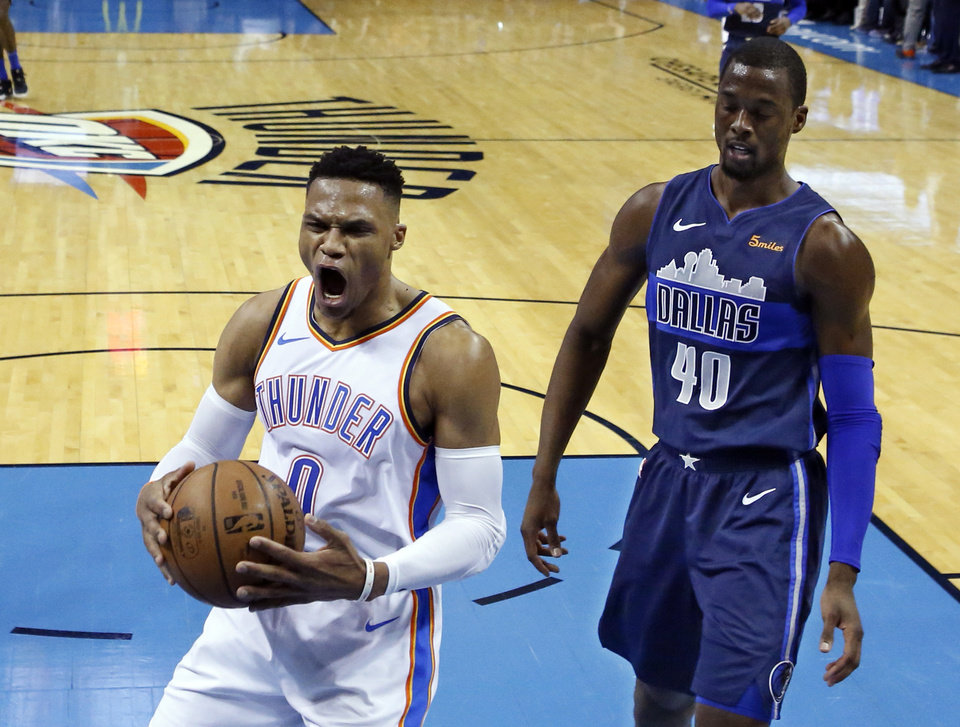 Photo - Oklahoma City Thunder guard Russell Westbrook (0) reacts to a dunk by a teammate in front of Dallas Mavericks forward Harrison Barnes (40) in the first half of an NBA basketball game in Oklahoma City, Monday, Dec. 31, 2018. (AP Photo/Sue Ogrocki)