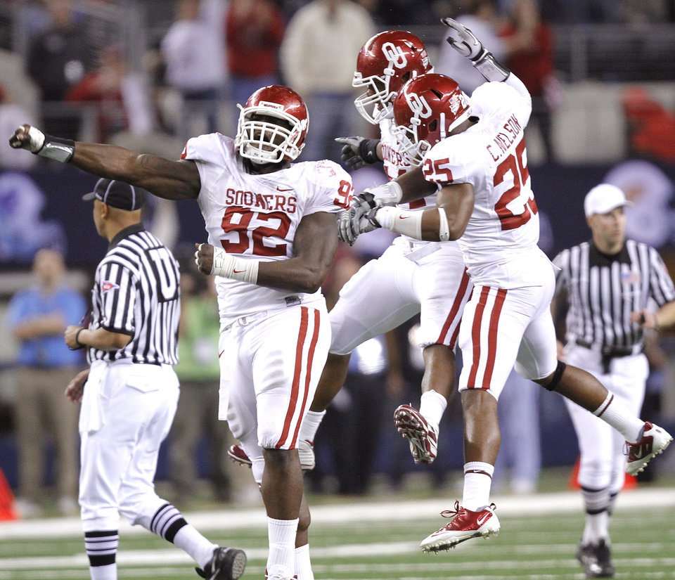 Photo - The Sooners' Stacy McGee (92) Jeremy Beal (44) and Corey Nelson (25) after stopping Nebraska on fourth down late in the fourth quarter to seal the 23-20 win in the Big 12 football championship game between the University of Oklahoma Sooners (OU) and the University of Nebraska Cornhuskers (NU) at Cowboys Stadium on Saturday, Dec. 4, 2010, in Arlington, Texas.  Photo by Chris Landsberger, The Oklahoman