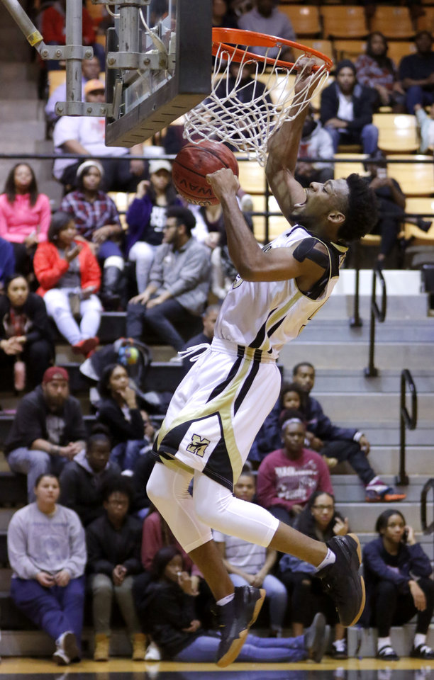 Photo - Midwest City's Keyshawn Embery-Simpson celebrates as he dunks during a high school basketball game against Putnam City West at Midwest City, Tuesday, Jan. 17, 2017. [Bryan Terry/The Oklahoman]
