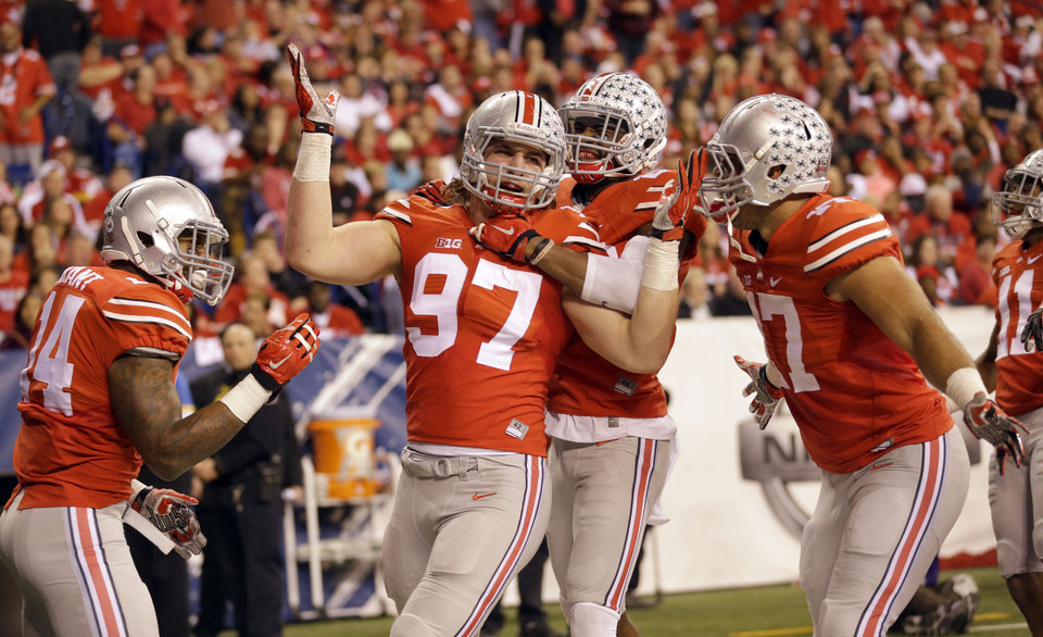 Photo - FILE - In this Dec. 6, 2014, file photo, Ohio State defensive lineman Joey Bosa (97) is congratulated by teammates after recovering a fumble and running it back for a touchdown during the first half of the Big Ten Conference championship NCAA college football game against Wisconsin in Indianapolis. Ohio State has suspended All-America defensive end Joey Bosa, receiver Corey Smith and H-backs Jalin Marshall and Dontre Wilson for its opening game at Virginia Tech. In a statement released about an hour before Big Ten media days began Thursday, July 30, 2015, the Buckeyes said the players violated department of athletics policy. (AP Photo/Michael Conroy, File)