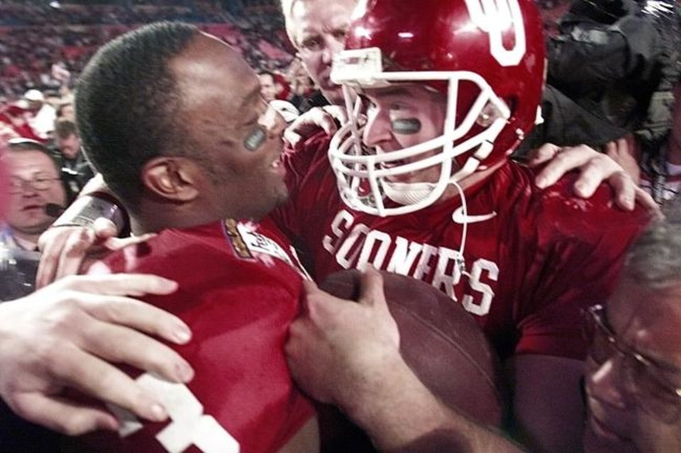 Photo -  Oklahoma quarterback Josh Heupel hugs Josh Norman after winning the Orange Bowl and the national championship by defeating Florida State 13-2 on Jan. 3, 2001, in Miami. [Robert Deutsch/USA TODAY]