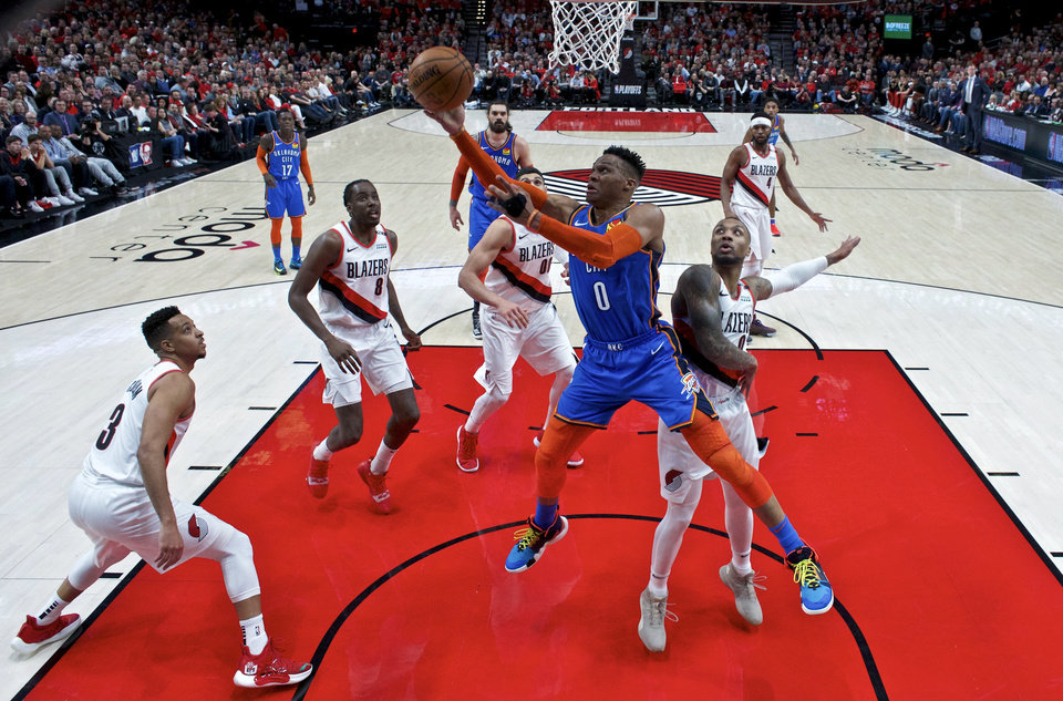 Photo - Oklahoma City Thunder guard Russell Westbrook, center, shoots over Portland Trail Blazers guard Damian Lillard, right, during the first half of Game 2 of an NBA basketball first-round playoff series Tuesday, April 16, 2019, in Portland, Ore. (AP Photo/Craig Mitchelldyer)