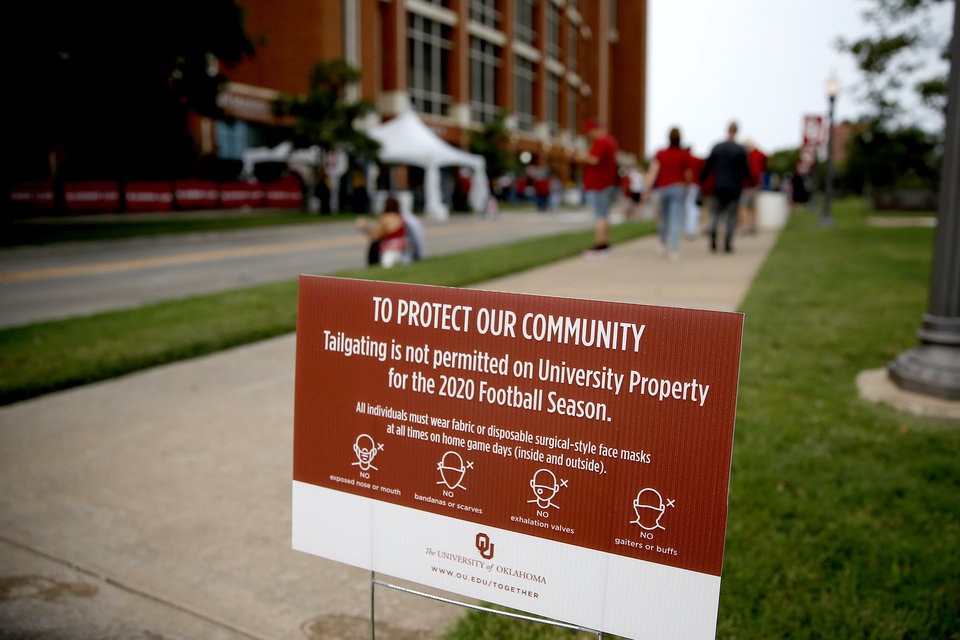 Photo - Fans walk past a sign displaying new game day policies before a college football game between the University of Oklahoma Sooners (OU) and Missouri State in Norman, Okla., Saturday, Sept. 12, 2020. [Bryan Terry/The Oklahoman]