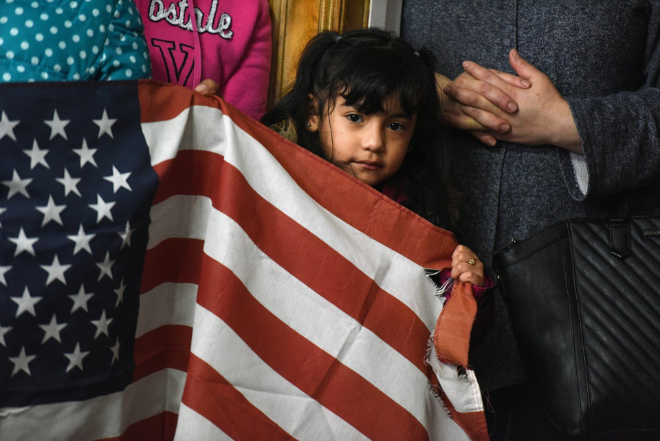 Photo - Maria Martinez, of Detroit, holds onto an American flag during a Michigan United press conference at its Detroit headquarters Thursday, Jan. 26, 2017, which called for protection of immigrant and Muslim community members after comments and actions made by President Donald Trump. (Tanya Moutzalias /The Ann Arbor News via AP)