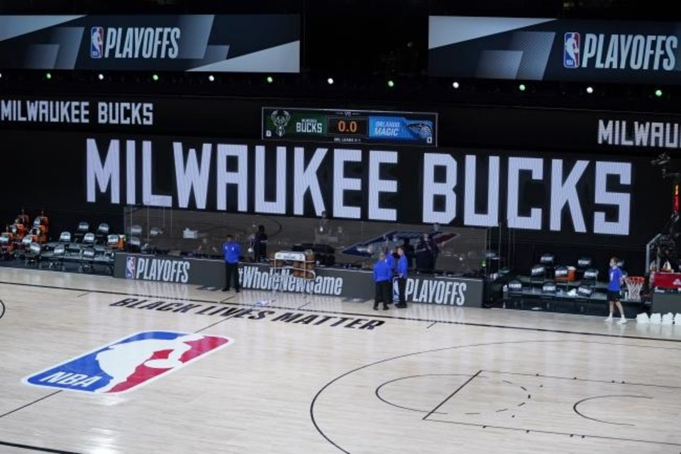 Photo -  Officials stand beside an empty court at the scheduled start of an NBA basketball first round playoff game between the Milwaukee Bucks and the Orlando Magic, Wednesday, Aug. 26, 2020, in Lake Buena Vista, Fla. The Milwaukee Bucks didn't take the floor in protest against racial injustice and the shooting of Jacob Blake, a Black man, by police in Kenosha, Wisconsin. (AP Photo/Ashley Landis, Pool)
