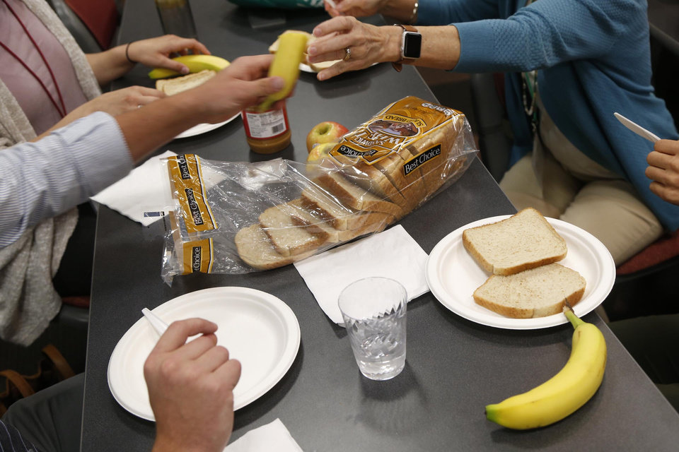 Photo - Students at OU-Tulsa's School of Community Medicine sit down to a lunch of peanut butter and banana sandwiches in Tulsa, Okla., on Monday, August 14, 2017. A class project had students shopping for a family of four with just a few dollars. MATT BARNARD/Tulsa World
