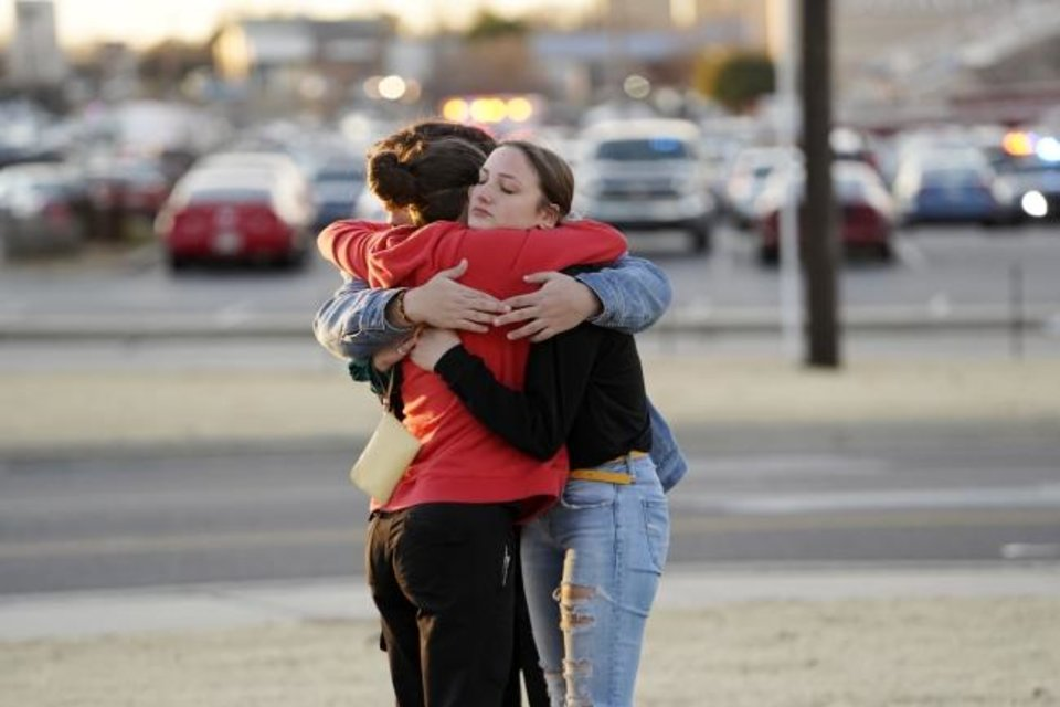 Photo -  Bystanders who were in the mall at the time of the shooting embrace after evacuating to the parking lot. [Nick Oxford, for The Oklahoman]