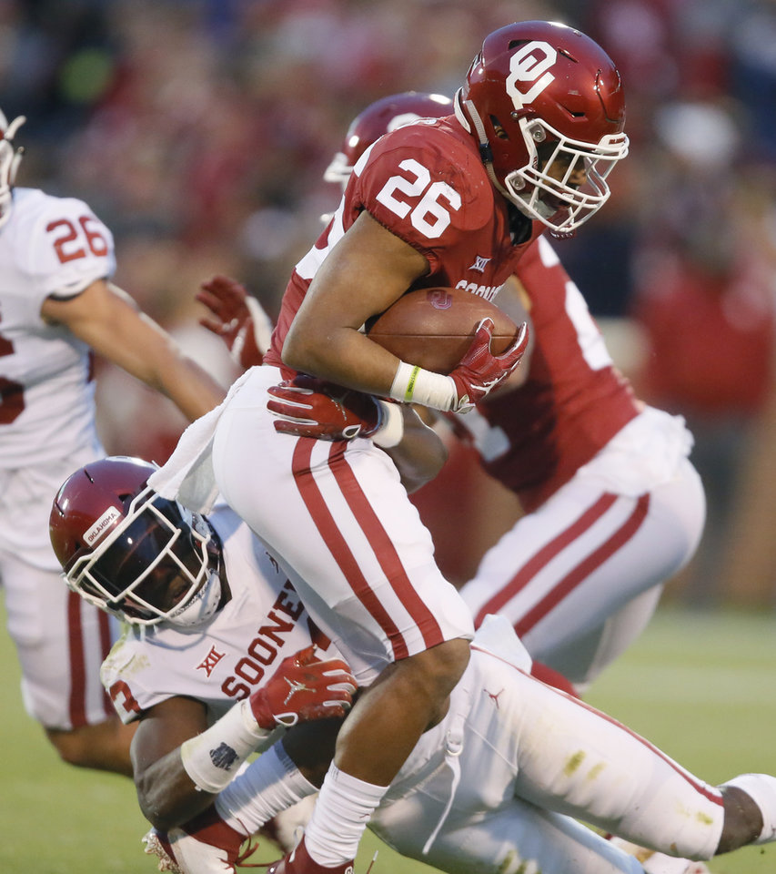 Photo - Oklahoma's Kennedy Brooks (26)  is brought down by Oklahoma's DaShaun White (23) during the University of Oklahoma (OU) spring football game at Gaylord Family-Oklahoma Memorial Stadium in Norman, Okla., Friday, April 12, 2019. Photo by Bryan Terry, The Oklahoman