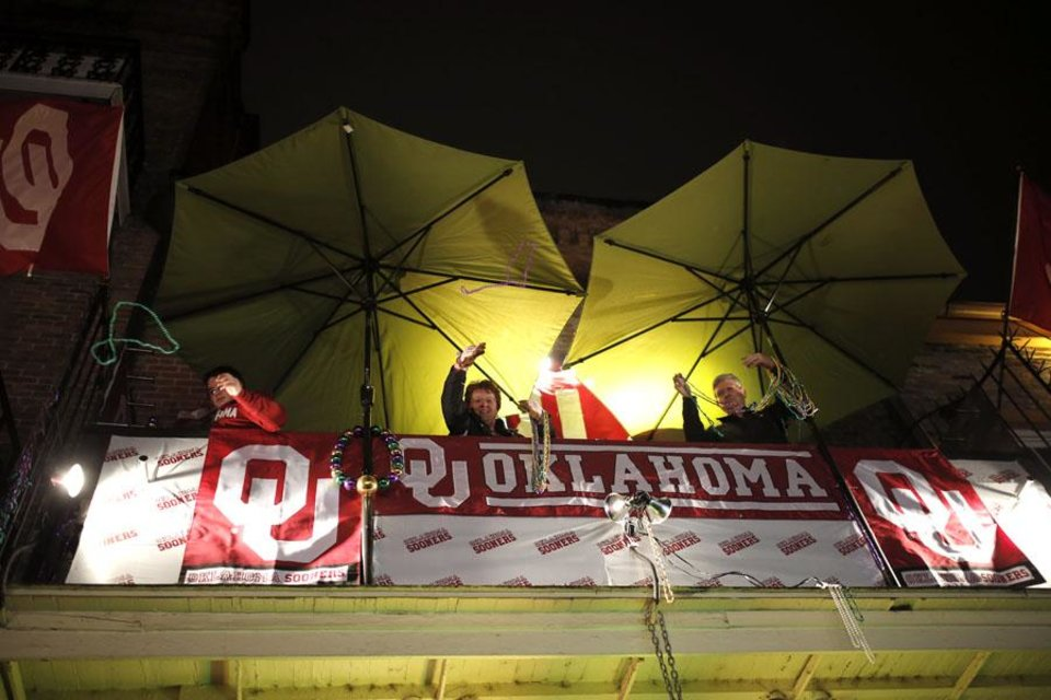 Photo -  Oklahoma fans throw beads from a balcony decorated with Sooner flags on Bourbon Street in the French Quarter New Year's Eve, Tuesday, Dec. 31, 2013 in New Orleans. Photo by Sarah Phipps, The Oklahoman