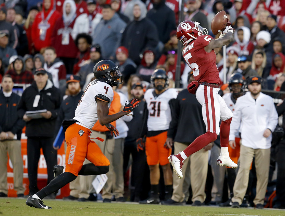 Photo - Oklahoma's Marquise Brown (5) makes a catch in front of Oklahoma State's A.J. Green (4) in the third quarter during a Bedlam college football game between the University of Oklahoma Sooners (OU) and the Oklahoma State University Cowboys (OSU) at Gaylord Family-Oklahoma Memorial Stadium in Norman, Okla., Nov. 10, 2018.  OU won 48-47. Photo by Sarah Phipps, The Oklahoman