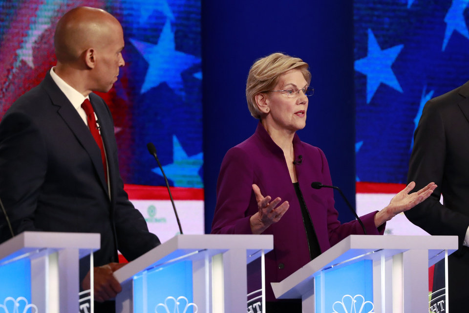 Photo - Democratic presidential candidate Sen. Elizabeth Warren, D-Mass., gestures during the Democratic primary debate hosted by NBC News at the Adrienne Arsht Center for the Performing Art, Wednesday, June 26, 2019, in Miami, as Sen. Cory Booker, D-N.J., listens. (AP Photo/Wilfredo Lee)