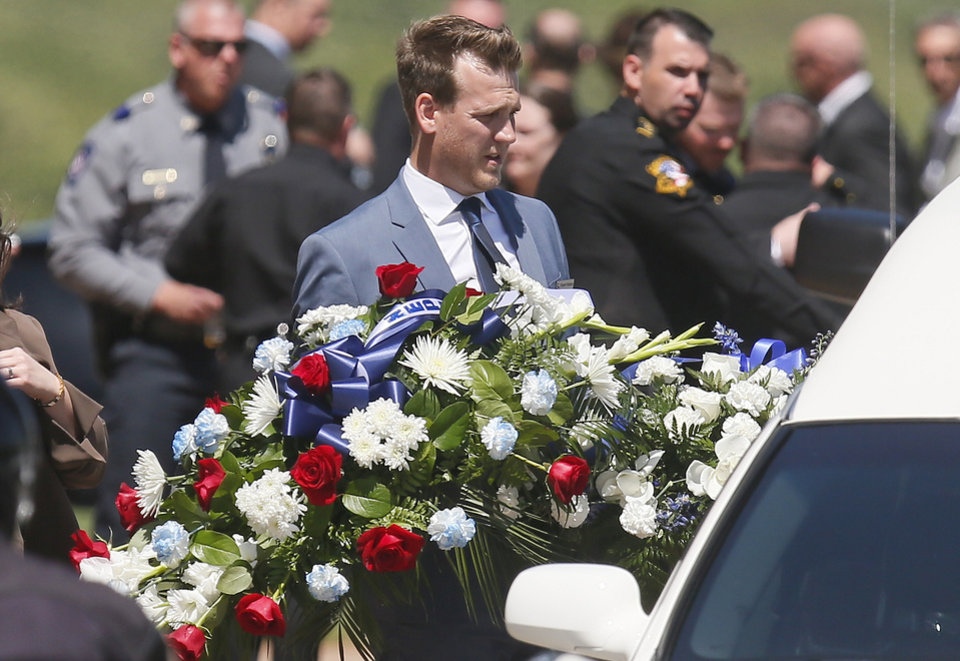 Photo - Flowers are carried to the hearse following the funeral of Logan County Deputy David Wade in Guthrie, Okla., Monday, April 24, 2017. Wade was shot and killed while serving an eviction notice near Mulhall, Okla,. on April 18. (AP Photo/Sue Ogrocki)