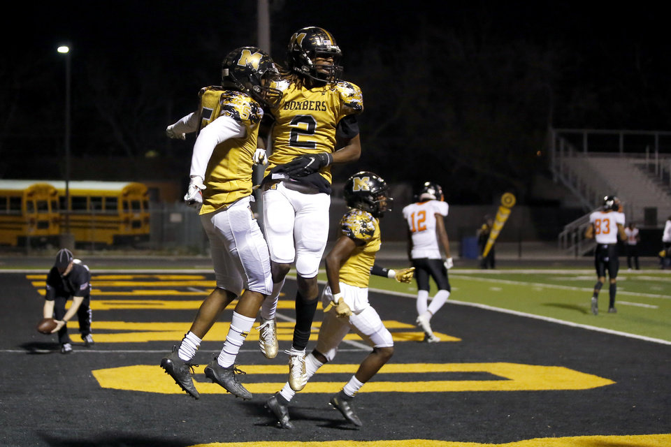 Photo - Midwest City's Makale Smith (2) and Brian Wilson Jr. of Midwest City celebrate after Wilson Jr. intercepted a pass during a high school football game between Midwest City and Tulsa Washington at Midwest City, Okla., Friday, Nov. 20, 2020. [Bryan Terry/The Oklahoman]