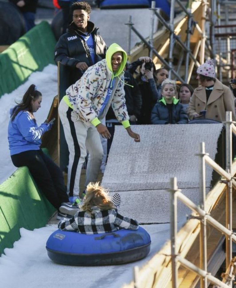 Photo -  Oklahoma City Thunder players Shai Gilgeous-Alexander, top, and Darius Bazley, watch a rider slide down a slope after giving her a push to start during a visit by Thunder basketball players to the LifeShare WinterFest at Chickasaw Bricktown Ballpark in Oklahoma City, Monday, Dec. 30, 2019. [Nate Billings/The Oklahoman]