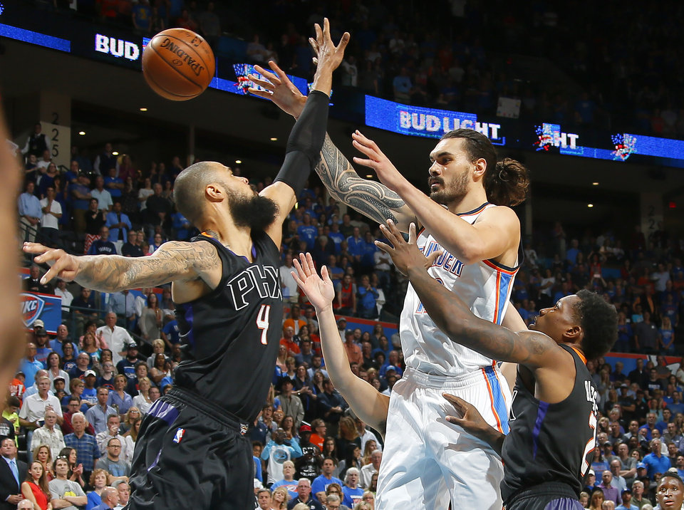 Photo - Oklahoma City's Steven Adams (12) passes from between Phoenix's Tyson Chandler (4) and Eric Bledsoe (2) during an NBA basketball game between the Oklahoma City Thunder and the Phoenix Suns at Chesapeake Energy Arena in Oklahoma City, Friday, Oct. 28, 2016. Photo by Bryan Terry, The Oklahoman