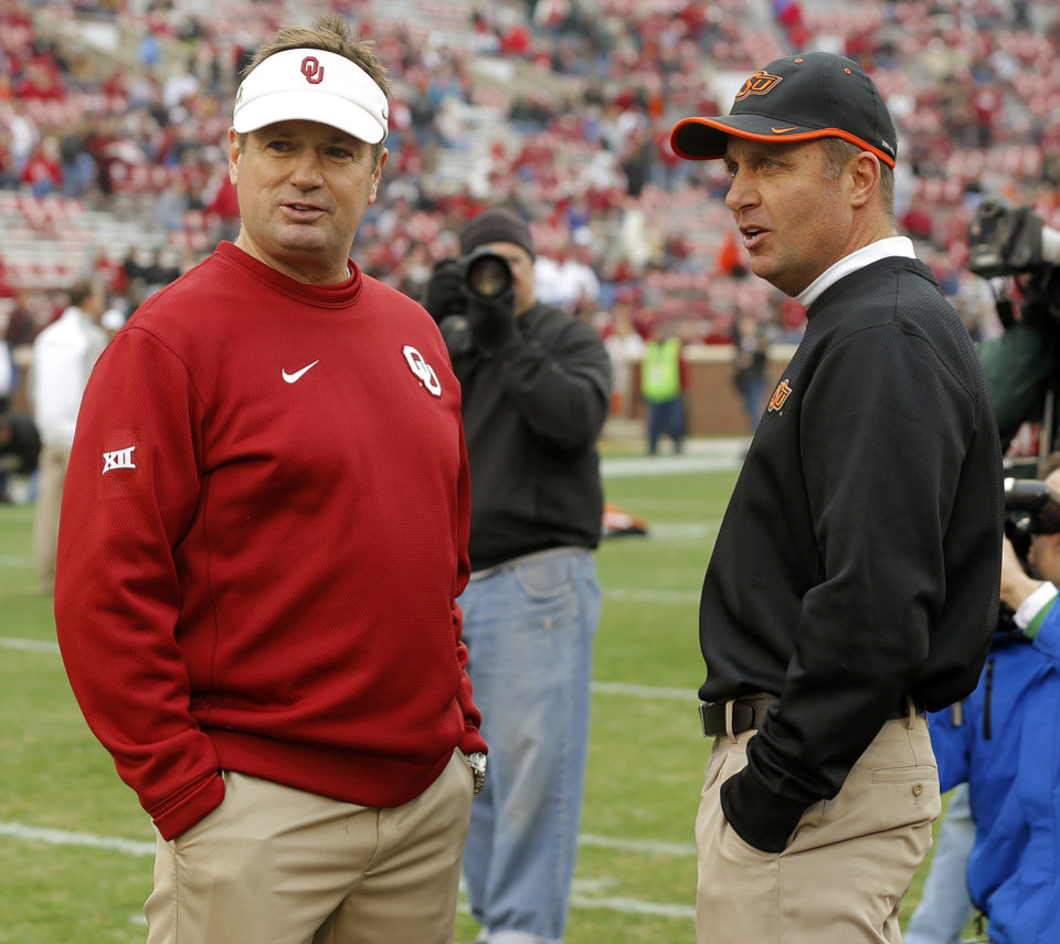 Photo - Oklahoma coach Bob Stoops and Oklahoma State coach Mike Gundy talk before a Bedlam college football game between the University of Oklahoma Sooners (OU) and the Oklahoma State Cowboys (OSU) at Gaylord Family-Oklahoma Memorial Stadium in Norman, Okla., Saturday, Dec. 6, 2014. Photo by Bryan Terry, The Oklahoman