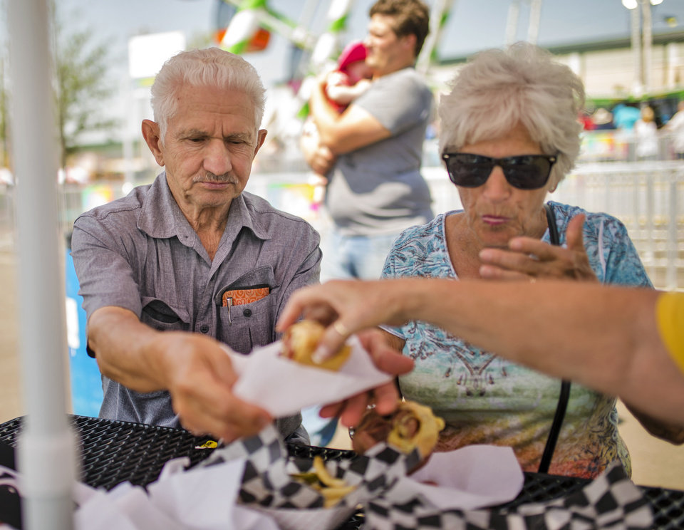 Photo - Bob Akerman and his sister Lou Hooper enjoy the Honey Bacon Pepper Dog from  Urb Express during the opening day of the 2017 Oklahoma State Fair in Oklahoma City, Okla. on Thursday, Sept. 14, 2017. Urb Express won the Great Taste of a Fair food award with its Honey Bacon Pepper Dog. Photo by Chris Landsberger, The Oklahoman