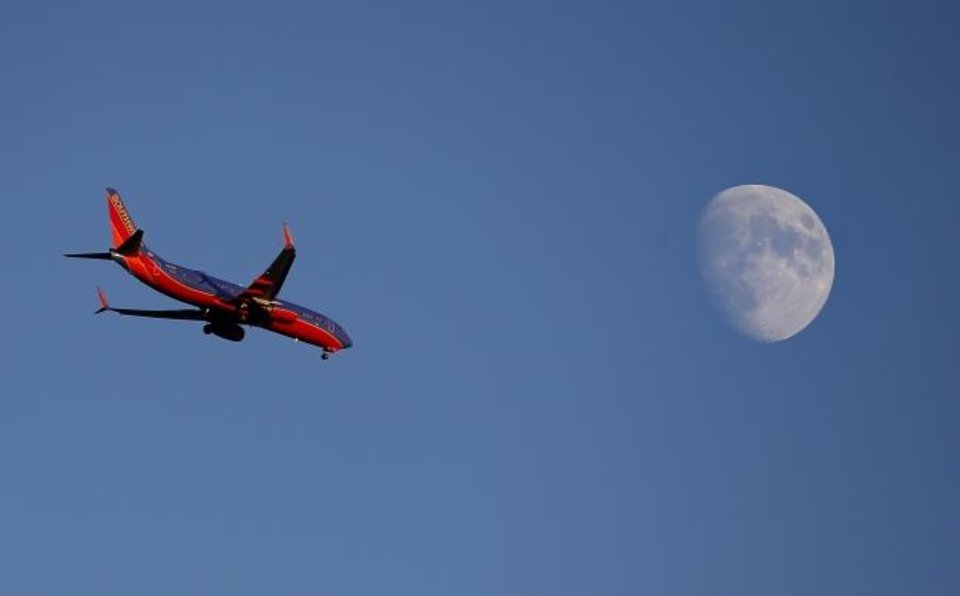 Photo -  A Southwest Airlines airplane appears to fly near the moon en route to Will Rogers Airport. [THE OKLAHOMAN ARCHIVES]