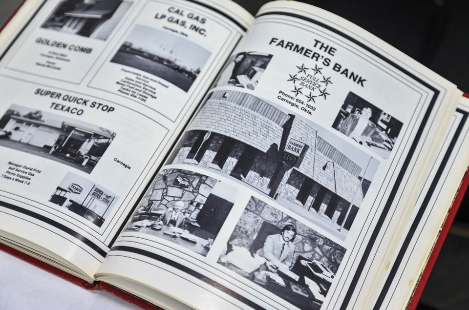 Photo -  Old Carnegie High School yearbook advertisements provide a glimpse of the history Farmers Bank. [Photo by Chris Landsberger, The Oklahoman]