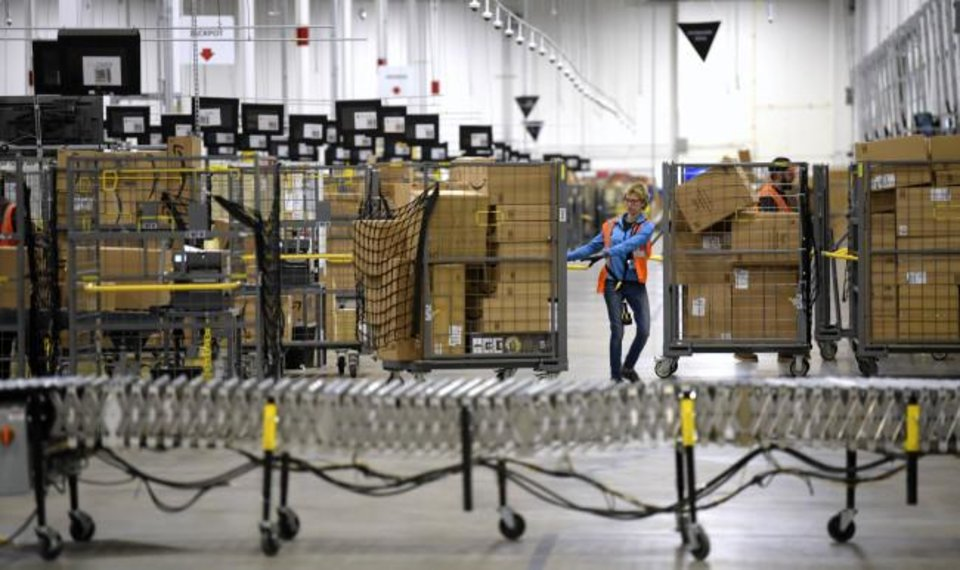 Photo -  Associates move bins filled with products in 2018 at the loading dock of Amazon's fulfillment center in Livonia, Mich. [Todd McInturf/Detroit News via AP, File]