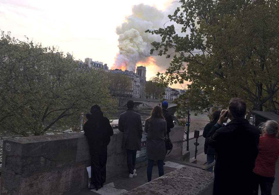 Photo - People watch Notre Dame cathedral burning in Paris, Monday, April 15, 2019. Massive plumes of yellow brown smoke is filling the air above Notre Dame Cathedral and ash is falling on tourists and others around the island that marks the center of Paris. (AP Photo/Oleg Cetinic)